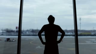 Silhouette of man in front of airport window