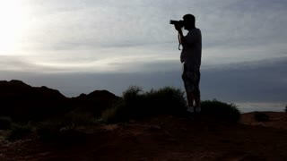 Silhouette of man photographing mountain
