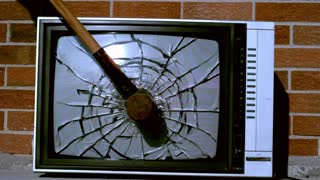 Sledge hammer smashing tv in slow motion