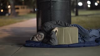 Sleeping homeless man on sidewalk at night 4k