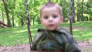 Small Child Swinging in Baby Swing