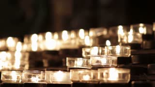 Small prayer candles burning in church