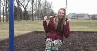 Smiling girl sitting on swing 4k