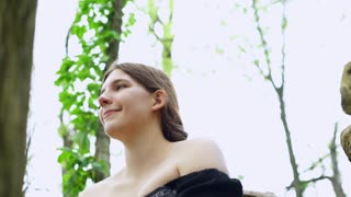 Smiling Renaissance girl sitting on log in woods 4k