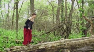Sneaky renaissance girl walking through woods 4k