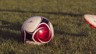 Soccer ball kicked by young female player slow motion