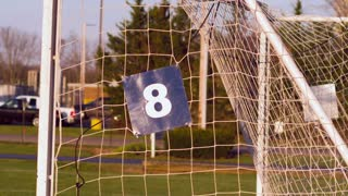 Soccer ball kicked into goal slow motion