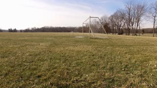 Soccer goal in winter with snow on field aerial shot 4k