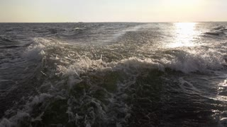 Splashing of waves behind boat with sunset in background 4k
