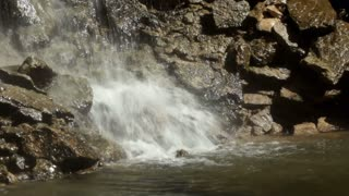 Splashing water on rocks below waterfall