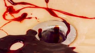 Splattering blood in bathroom sink slow motion