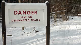 Stay on trail sign on winter path