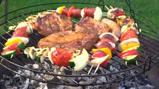 Steak and Kabob cooked on grill over fire pit 4k