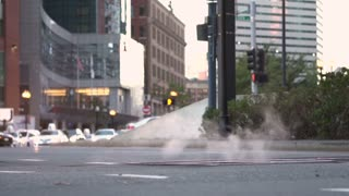 Steam coming from city street manhole slow motion