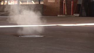 Steam coming out of manhole in downtown city 4k