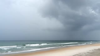 Storm coming in on ocean shore with black sky