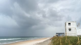 Storm front moving in on beach with cloudy sky