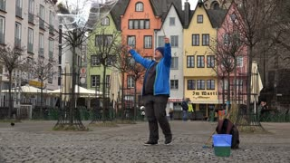 Street performer in Cologne Germany making large soap bubbles 4k