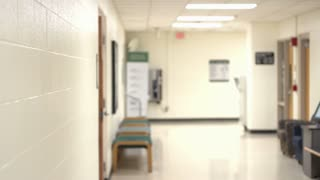 Student walking through hallway pan