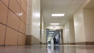 Students walking down hallway followed by man 720p