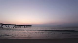 Sunrise at ocean pier with beach and waves
