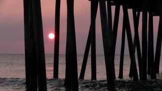 Sunrise at ocean seen from under dock