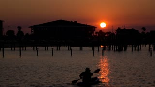 Sunset on ocean shore with kayak going by slow motion