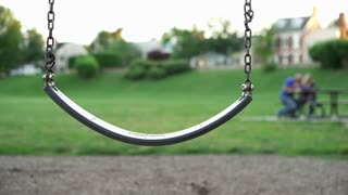 Swing at park with couple sitting in background 4k