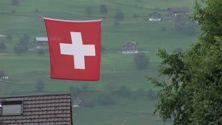 Swiss flag with houses in mountains