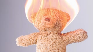 Teddy bear toy of child on fire slow motion