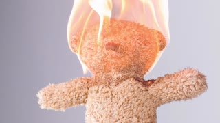 Teddy bear with head on fire slow motion