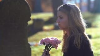 Teen girl sitting at grave thinking