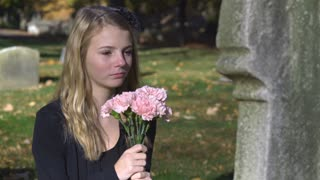 Teen upset and sad sitting at grave with flowers 4k