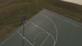Teenage boy practicing basketball on court aerial view 4k