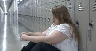 Teenage female sitting on floor of high school hallway upset 4k