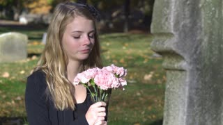 Teenage girl sitting at gravestone with flowers in hand 4k