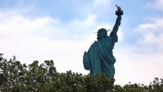 The United States Statue of Liberty towering over trees 4k