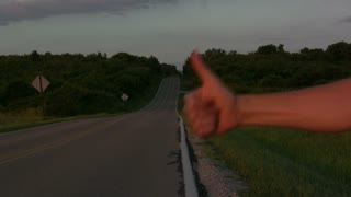Thumb Hitch hiking on side of road
