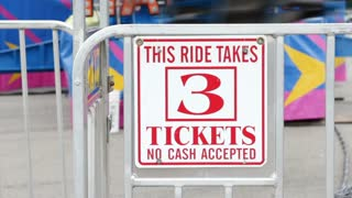 Ticket sign at carnival with ride in background