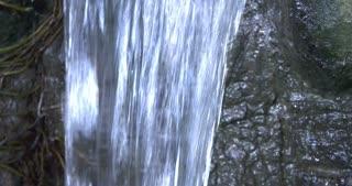 Tilt of small waterfall water flowing down rock 4k