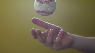 Tossing baseball in hand slow motion
