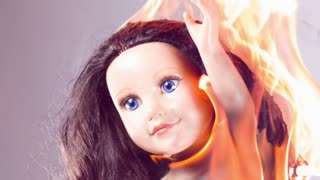 Toy doll of child burning in fire slow motion