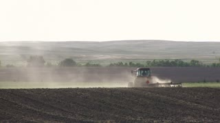Tractor going over hill of crop field