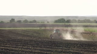 Tractor going through field digging up ground