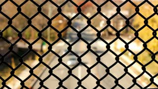 Traffic below seen through chain link fence