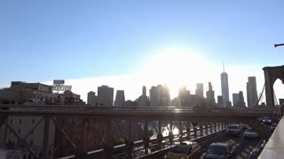 Traffic crossing Brooklyn Bridge with NYC in background 4k