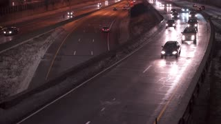 Traffic going down highway at night with snow on road 4k