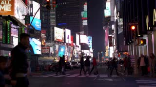 Traffic in Times Square with pedestrians crossing street 4k