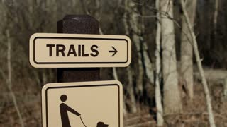 Trails sign to dirt path rack focus and pan