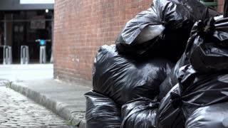 Trash bags in side street establishing shot of city 4k